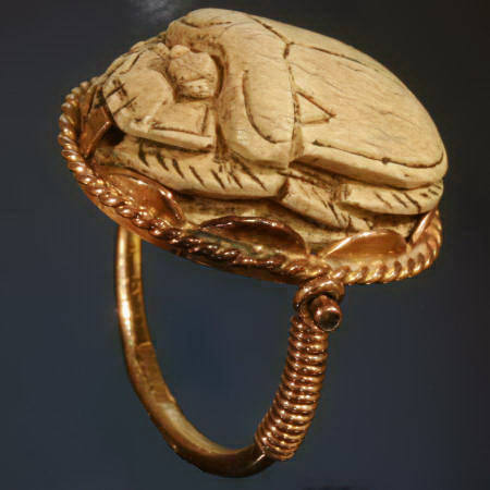 Typical Egyptian scarab ring with cartouched scarab set in golden swivel ring